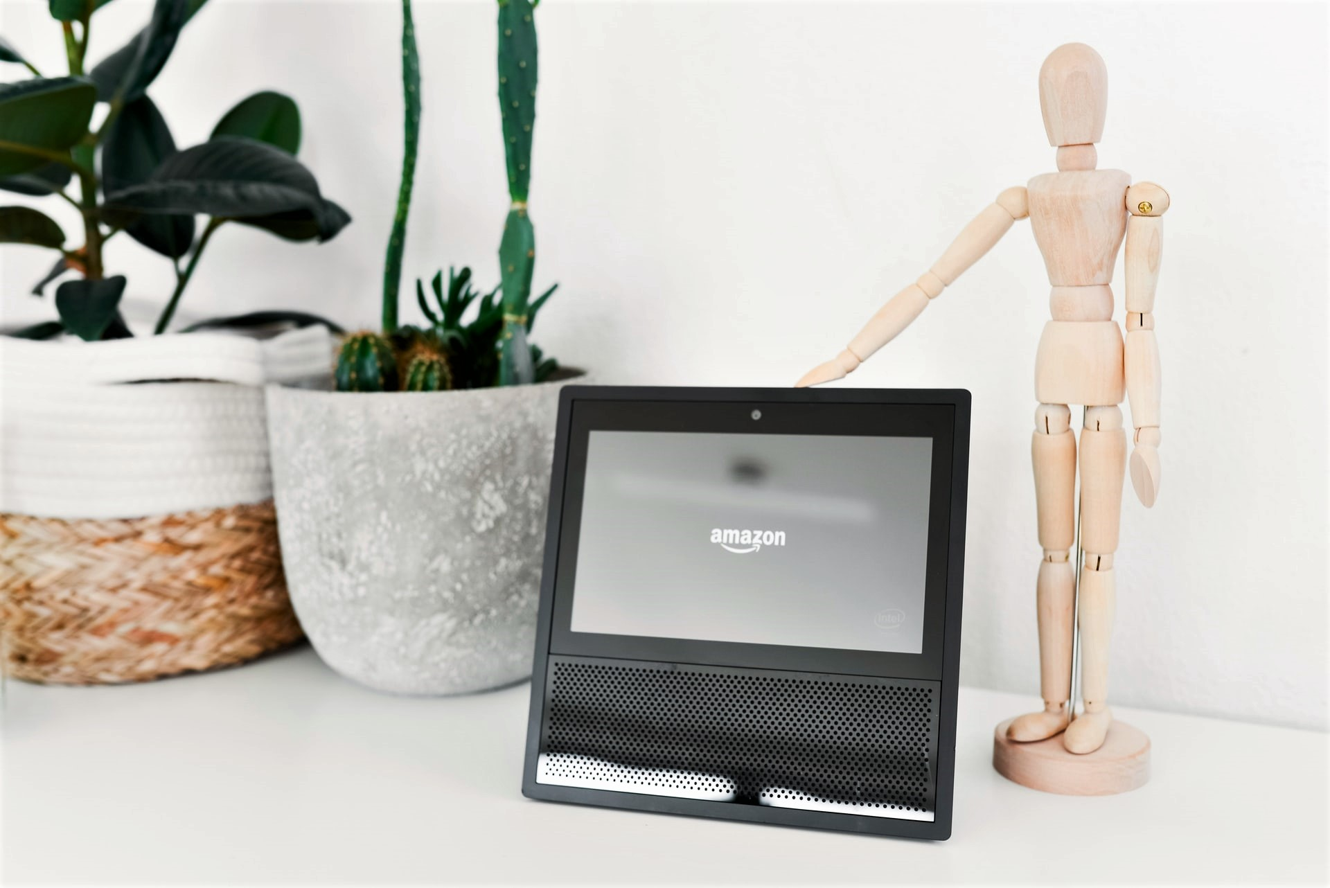 wooden mannequin standing next to an Echo show device on a white table.