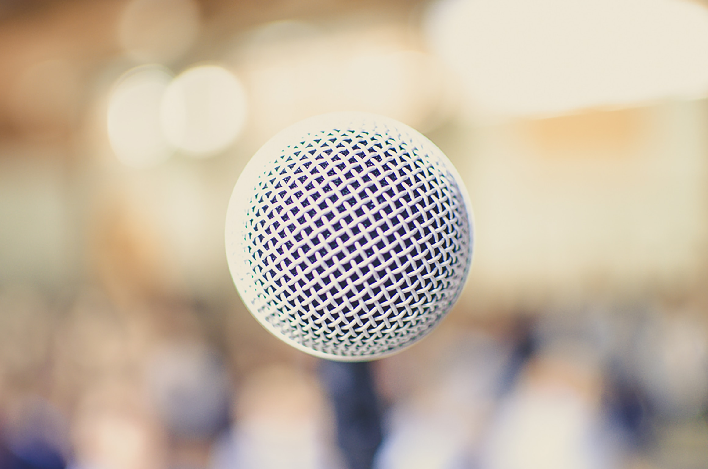 The top of a microphone and a hazy yellow background.
