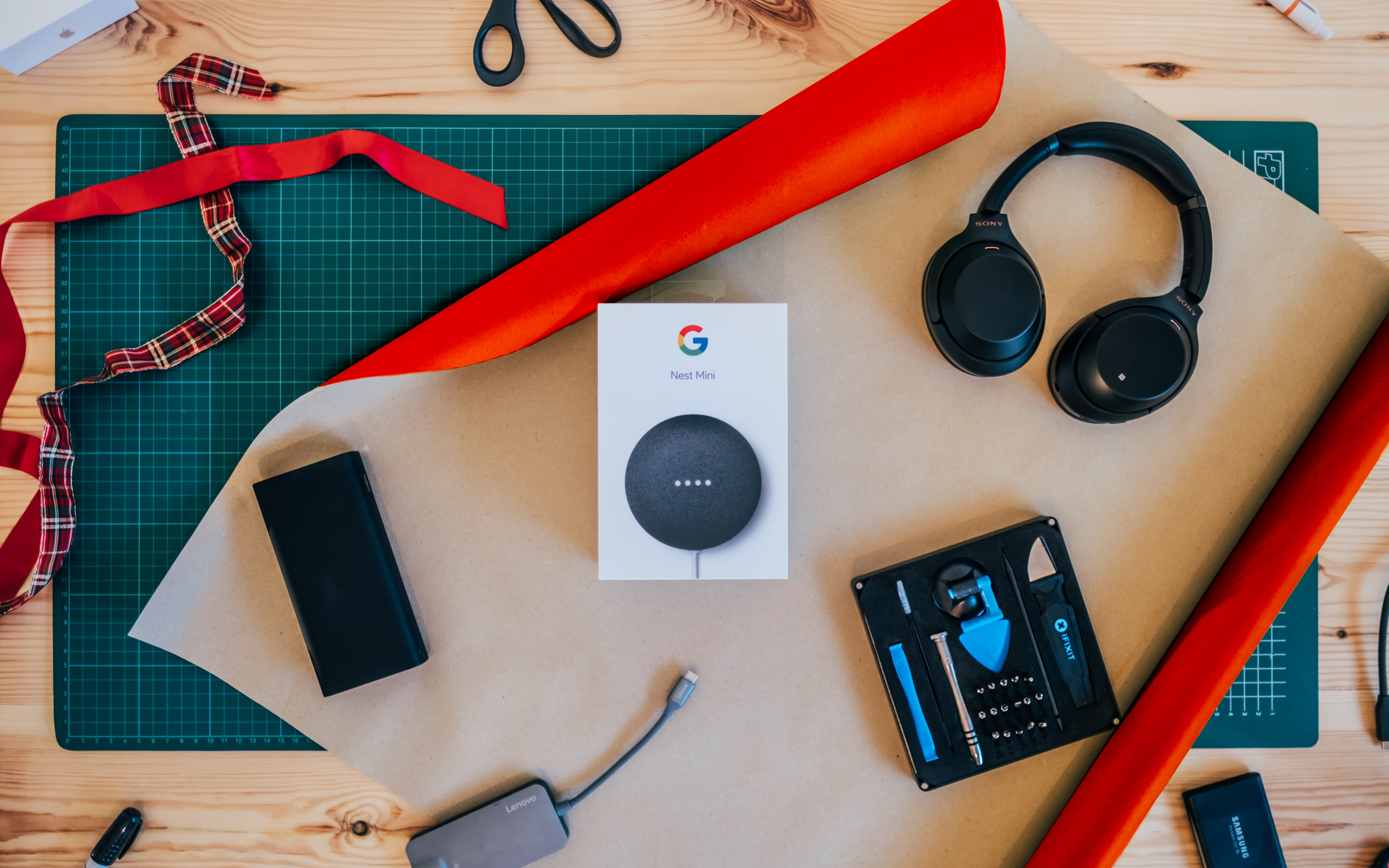 Google mini on a table surrounded by different electronics